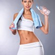 Portrait of a healthy woman with bottle of water and towel. — Stock Photo