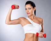 Beautiful young woman with dumbbells — Stock Photo