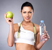 Healthy woman with apple and bottle of water — Stock fotografie