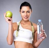 Zdravá žena s apple a láhev vody — Stock fotografie
