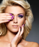 Beautiful woman with beauty purple manicure and makeup of eyes. — Stock Photo