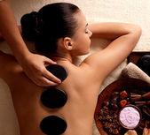 Kobieta zaczyna masaż gorącymi kamieniami w salonie spa. — Zdjęcie stockowe