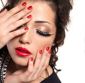 Model with red nails, lips and creative eye makeup — ストック写真