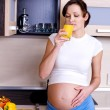 Pregnant woman drinks orange juice — Stock Photo #1591790