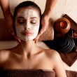 Spa massage for woman with facial mask on face — Stock Photo