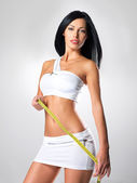 Sporty beautiful woman with measure tape — Stock Photo