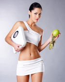Healthy woman stands with the scales and green apple. — Stock Photo