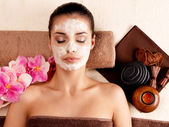 Woman relaxing with cosmetic mask on face — Stock Photo