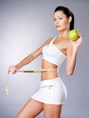 Slimming woman with a measuring tape and apple — Stock Photo