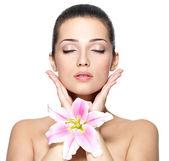 美的漂亮女人与花的脸。美容治疗概念 — 图库照片