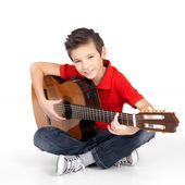 Happy boy is playing on acoustic guitar — Stock Photo