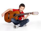 Smiling boy is playing the acoustic guitar — Stock Photo