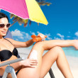 Stock Photo: Womin bikini applying sun block cream on body