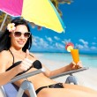 Woman on vacation at beach with thumbs up sign — Stock Photo