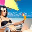 Happy woman on the beach with a laptop — Stock Photo #19124159
