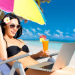 Happy woman on the beach with a laptop - Stock Photo