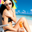 Stock Photo: Woman in bikini applying sun block cream on body