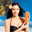 Woman on the beach  holds orange sun tan lotion bottle. - Stock Photo