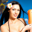 Woman on the beach  holds orange sun tan lotion bottle. — Stock Photo