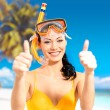 Happy woman on beach with thumbs up sign — Stock Photo