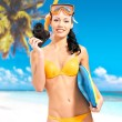 Woman with a camera taking photos on beach — Stock Photo #19124501