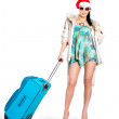 Woman in santa hat standing with travel suitcase — Stock Photo