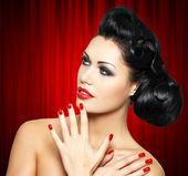 Mujer de moda con labios rojos, uñas y peinado creativo — Foto de Stock