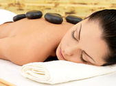 Massaggio stone per donna al salone spa. — Foto Stock