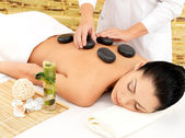 Woman having hot stone massage of back in spa salon — Stock Photo