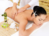 Woman on therapy massage of back in spa salon — Stok fotoğraf