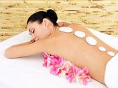 Woman at spa salon. White нot stones on female back. — Stock Photo