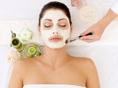 Young woman at spa salon with cosmetic mask on face — Stock Photo