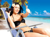 Happy woman with a video camera on beach — Stock Photo