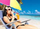 Glad kvinna på semester njuter på stranden — Stockfoto