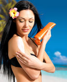 Woman in bikini applying sun block cream on body — Stock Photo