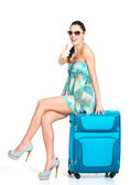 Woman with suitcase and shows thumbs-up sign — Stockfoto