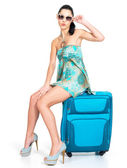 Сasual woman standing with travel suitcase — Stock Photo