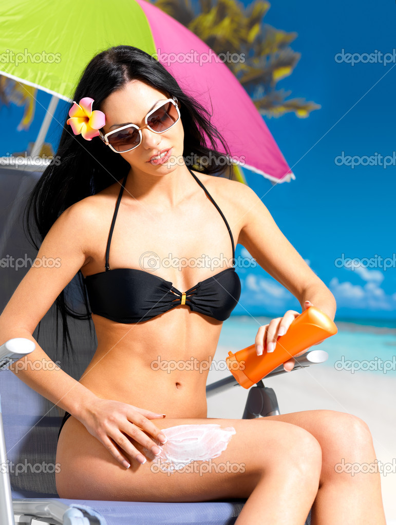 Beautiful young woman in black bikini applying sun block cream on the tanned body.  Girl  holding orange sun tan lotion bottle. — Stock Photo #19124287
