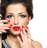 Beautiful fashion model with red manicure and lips — Stock Photo