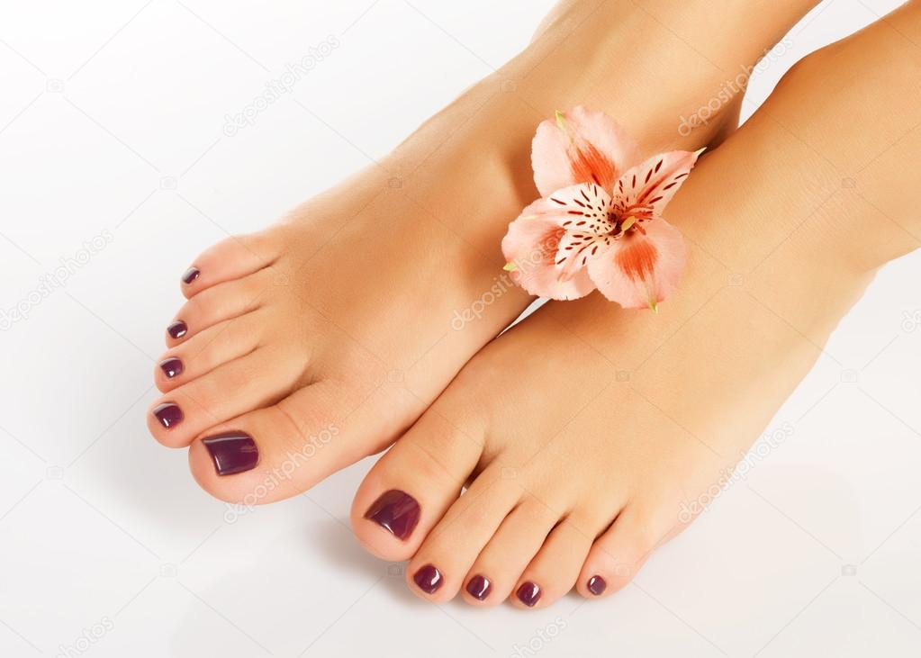 Female feet with beautiful pedicure after spa procedure ...