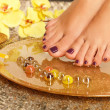 Female feet at spa salon on pedicure procedure - Stock Photo