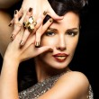 Beautiful woman with golden nails and style makeup — Stock Photo