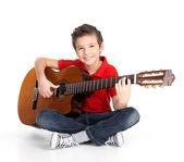 Menino feliz está a tocar no violão — Fotografia Stock