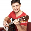 Smiling guitarist plays on the acoustic guitat — Stock Photo