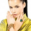 Woman with golden nails and precious stone emerald - Stock Photo