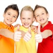 Happy children with thumbs up gesture — Stockfoto