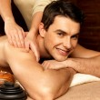 Smiling man having massage in the spa salon — Stock Photo
