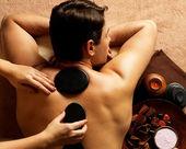 Man having stone massage in spa salon — Stock Photo
