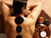 Man having stone massage in spa salon — Stock Photo