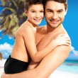 Stock Photo: Happy smiling father hugs son at tropical beach